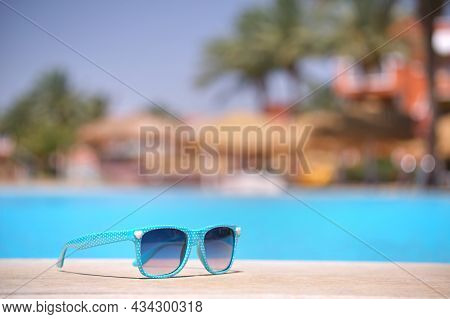 Closeup Of Blue Sunglasses On Swimming Pool Side At Tropical Resort On Warm Sunny Day. Summer Vacati