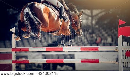 Equestrian Sport, Jumping. Overcome Obstacles. Jumping Competition. The Shod Hooves Of A Horse Over