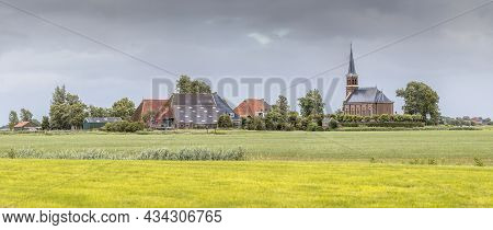 Dutch Hamlet Of Warstiens With Church And Several Farm Barns In Dairy Landscape Near City Of Leeuwar