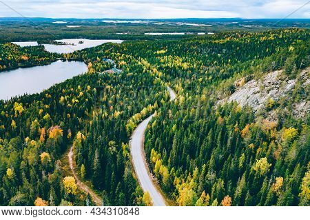 Aerial View Of Rural Road In Yellow And Orange Autumn Forest With Blue Lake In Finland