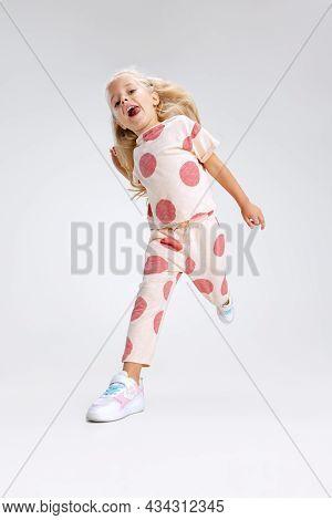 Full-length Portrait Of Little Caucasian Girl, Child Posing Running Isolated Over White Studio Backg