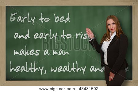 Teacher Showing Early To Bed And Early To Rise Makes A Man On Blackboard