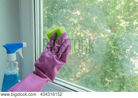 Woman's Hand In A Lilac Rubber Glove Wipes A Glass Unit Window In A Room With A Sponge. The Concept