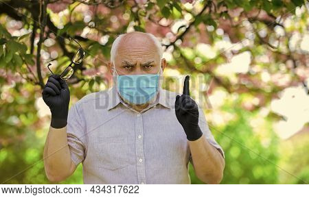 Highly Recommend. Wear Mask In Blossoming Pink Sakura Park. Man At Sakura In Protective Mask. Smell