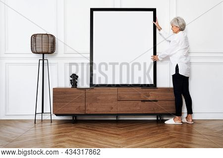 Senior woman adjusting a blank photo frame on a wooden cabinet in a Japandi living room