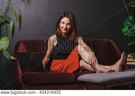 Attractive Businesswoman With Red Hair In Red Skirt And Black Sleeveless Blouse Sits On Couch With L