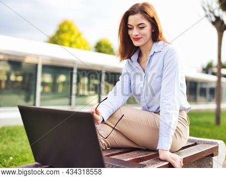 Young Redhead Caucasian Woman Smiling Into Laptop At Outdoors At City Park