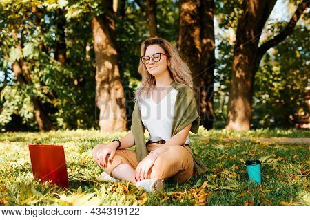 Smiling Young Woman Freelancer Meditates, Relaxes During Remote Work Outdoors. Teenage Girl With Gla