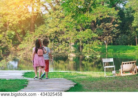 Back View Of Asian Young Girl And Boy Walking Together On Pathway Through Green Garden. Sister And B