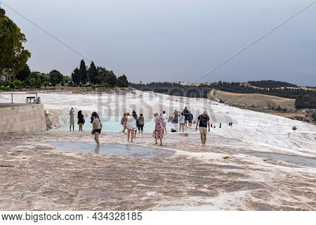 Pamukkale, Turkey - 1 June, 2021: Unidentified Tourists Walk Barefoot Through Travertine Pools Forme