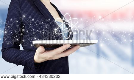 Atom Molecule As Concept For Science. Hand Hold White Tablet With Digital Hologram Molecule Atom Sig