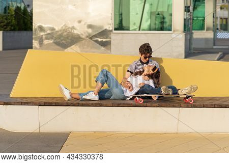 Young Hipster Couple Has Fun Cuddling Sit On Longboard Enjoy Summer Sunset In Urban City Park. Styli