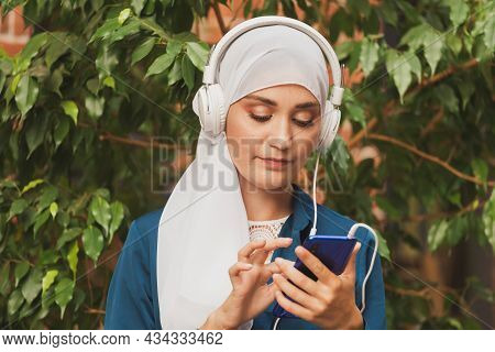 Portrait Of Young Modern Arabian Woman Holding Mobile Phone And Listening The Music To Headphone.