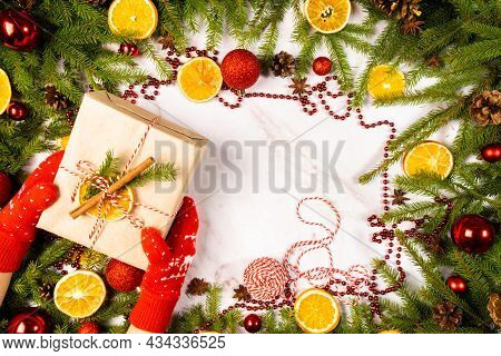 Branches Of A Christmas Tree With A Gift Box, Cones, Christmas Balls , Slices Of Orange On A Light B