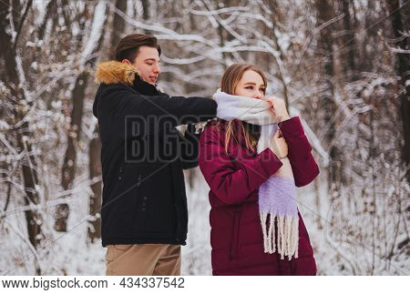 Photo Of Beautiful Young Teen Couple Spending Time Together Outside In Cold Winter, Guy Straightenin