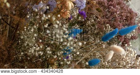 Large Floral Arrangement Bouquet Of Dried Flowers On The Background Of A Wood Wall And Cement Floor.