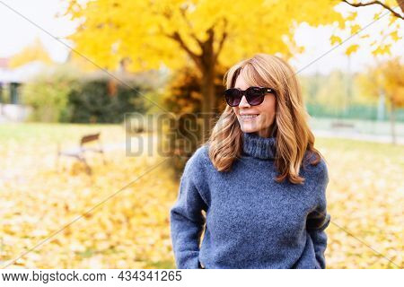 Attractive Middle Aged Woman Using Her Mobile Phone And Text Messaging While Walking Outdoor In The