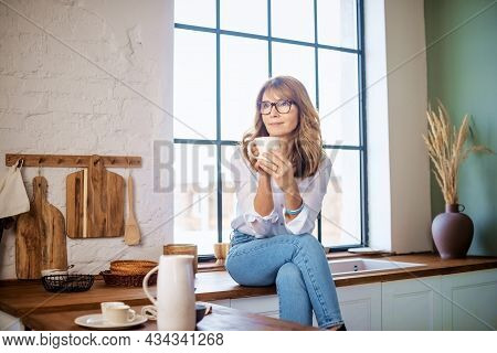 Middle Aged Woman Sitting On The Kitchen's Counter And Drinking Her Morning Tea While Daydreaming.
