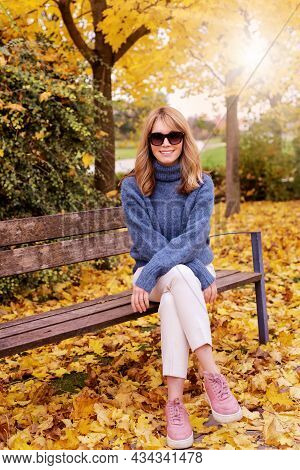 Full Length Of Happy Woman Sitting On The Bench In The Park And Enjoying Fall Weather.