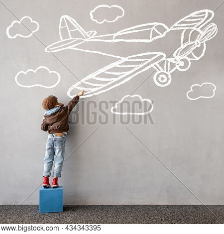 Dream Big! Happy Kid Draws A Chalk Airplane On The Wall. Children Imagination And Travel Concept