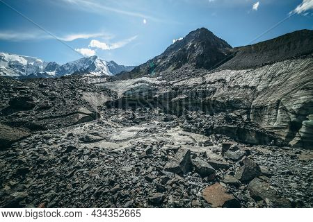 Scenic Highlands Landscape With Big Cracked Glacier With Scratches Among Moraines On Background Of H