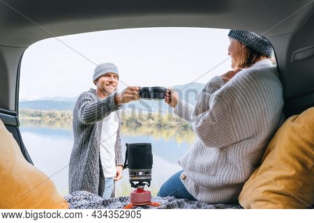 Car Trunk View Clinking Tea Mugs Couple Dressed Warm Knitted Clothes Enjoying Gas Stove Prepared Dri