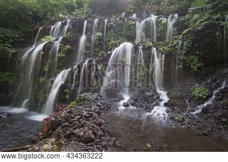Waterfall In The Forest. Bali Natural Waterfalls With Smooth Water On Green Forest Backgrounds. Wate