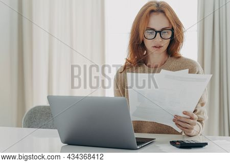 Serious Redhead Caucasian Woman Calculates Bills Holds Paper Documents Has Focused Look Uses Laptop