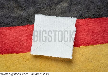 blank sheet of white paper against abstract in colors of Germany national flag - black, red and gold, October is German American Heritage Month