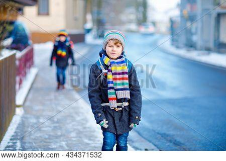 Two Little Kids Boys Of Elementary Class Walking To School During Snowfall. Happy Children Having Fu
