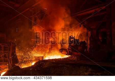Molten Metal Flows Through The Channel. Blast Furnace Metal Release, A Lot Of Smoke.