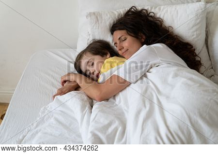 Peaceful Loving Mother Hugging Preschool Boy Sleeping Together With Child In Cozy Bed Under Warm Bla