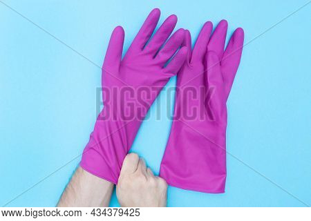 Man Puts On Protective Rubber Gloves. Purple Gloves For Cleaning. Flat Lay. Protection Of Skin And H