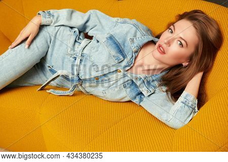Portrait of a beautiful blonde girl posing in denim overalls on a bright yellow sofa in a modern apartment. Modern interior and furniture. Fashion shot.