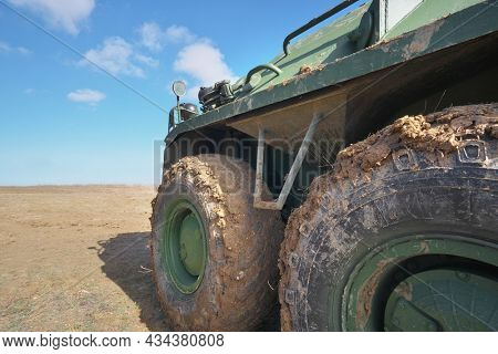Armored personnel carrier wheels in the mud at field.