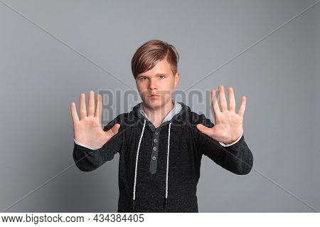 Portrait Of Serious Teenager Boy Doing Stop Sign With Palm Of The Hand With Negative And Serious Fac