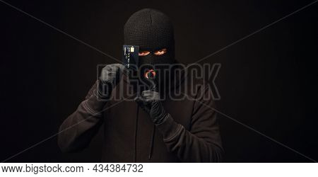 Thief in black balaclava holding black credit card. Banking and non cash thief concept