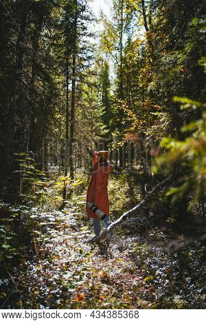 Caucasian Girl In A Pink Raincoat With A Large Telephoto Lens In Her Hands Stands In The Rays Of The