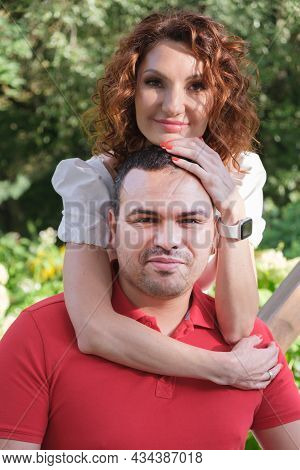 Vertical Portrait Of A Couple In Love. Woman Stands And Hugs Her Husband From Behind. Man In A Red T