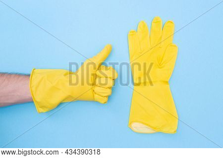 Man In Protective Rubber Yellow Glove. Symbol Like. Rubber Gloves For Cleaning On A Blue Background.