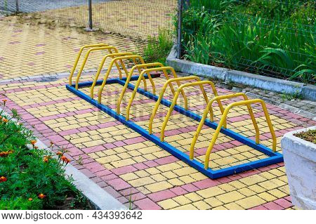 Metallic Elements Of Urban Architecture For Bicycle Parking Near Buildings In The City. Background W