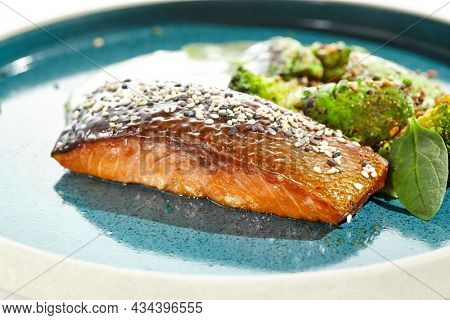 Roast salmon with crispy skin, grilled vegetables and espuma. Grilled salmon fillet with broccoli, avocado and white sauce. Keto food - baked fish with skin and green vegetables on white background