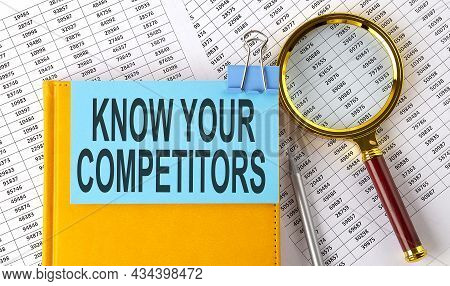 Know Your Competitors Text On Sticker On Notebook With Magnifier And Chart. Business