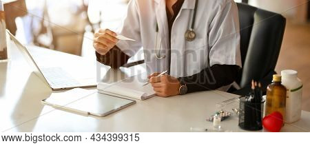 Doctor Or Physician Taking His Patient's Temperature With A Medical Thermometer