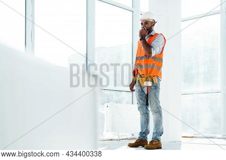 Young Construction Worker In Uniform Using Walkie Talkie On Site