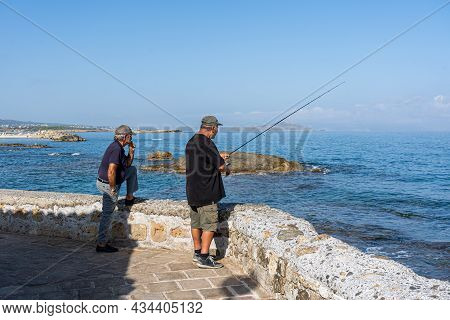 Chania, Greece - September 22, 2021: Two Men Fishing With A Fishing Rod In The Historic City Centre