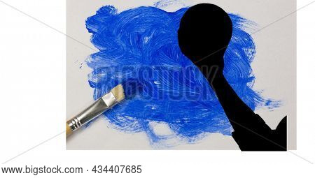 Mid section of silhouette of female handball player against blue paint stain and paint brush. sports and competition concept
