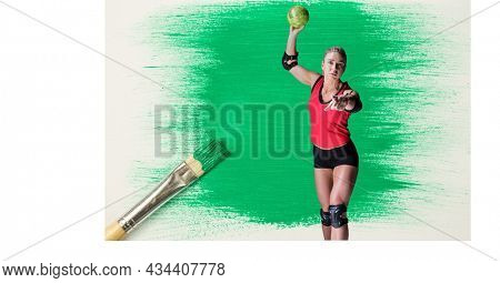 Caucasian female handball player against green paint stain and paint brush on white background. sports and competition concept