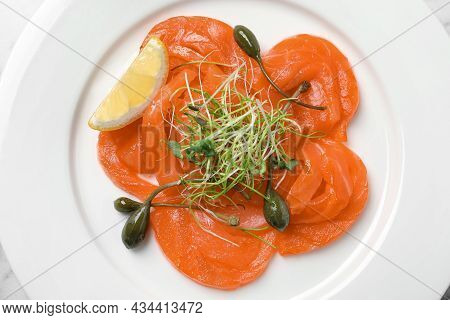 Salmon Carpaccio With Capers, Microgreens And Lemon On Plate, Top View