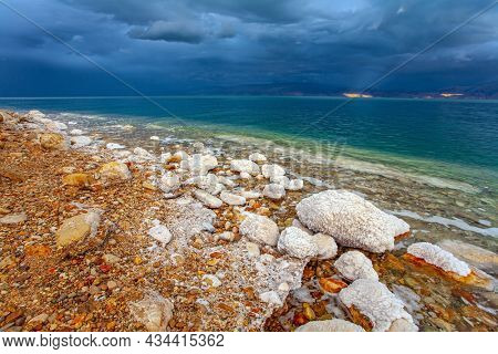 Rocky beach covered with evaporated salt. The Dead Sea is a closed salt lake. Gloomy sky with dark thunderclouds. Magnificent exotic resort for treatment and relaxation. Israeli coast.